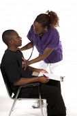 African American nurse with stethoscope checking the heart of a male African American patient