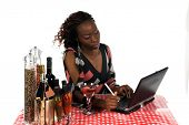 Pretty young African American business woman working on a laptop computer while enjoying a beverage