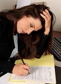 Female executive filling out tax forms while sitting at her desk