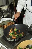 Detail of a line chef preparing Chinese food, Broccoli Chicken in a wok