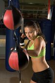 A beautiful young woman fighter training on a double ended speed bag in an MMA gym
