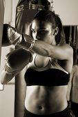 Dedicated young female fighter throwing a flurry of punches on the heavy bag Motion blur on her hand