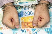 Businessman In Office In Handcuffs Holding A Bribe Of Israeli Money. Close-up Hands In Handcuffs. Ar poster