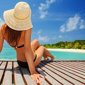 Young fashion woman relax on the beach. Happy island lifestyle. White sand, blue cloudy sky and crys poster