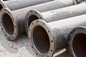 stock photo of sandblasting  - Flanged pipes covered with sand for sandblasting - JPG
