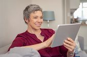 Smiling senior woman looking her digital tablet while sitting on sofa. Portrait of mature happy woma poster