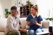 Female healthcare worker sitting with a senior Hispanic man in his living room during a home visit poster