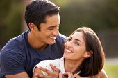Young Hispanic couple looking at each other smiling, close up poster