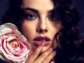 Beautiful face of a young woman with a smoky eye makeup  and rose flower. Sexy  brown-haired woman w poster