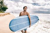 Surfer man going surfing on maui beach hawaii, usa. Professional male athlete carrying blue surf lon poster