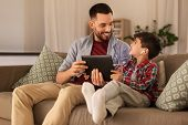 family, fatherhood and technology concept - happy father and little son with tablet pc computer and  poster