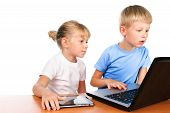 Overwhelmed Elementary Boy And Girl Sitting At Table Using Digital Pad And Laptop