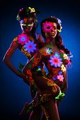 Nude women with glow uv body art and flowers