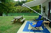 picture of lawn chair  - RV with lawn chairs and picnic table parked with river and trees in background - JPG
