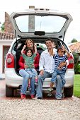 image of car ride  - Happy family sitting in the trinck of their car - JPG