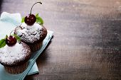 stock photo of chocolate muffin  - fresh chocolate muffins with cherry - JPG
