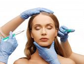 cosmetic surgery concept - woman face and beautician hands with syringes