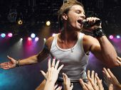 stock photo of adoration  - Young man singing on stage in concert with adoring fans reaching towards him - JPG