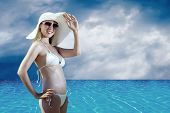 Beautiful happiness girl in white hat on ther beach