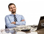 stock photo of revenue  - cheerful and successful businessman at his desk with laptop and a lot of money  - JPG