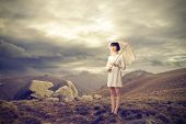 beautiful woman with vintage dress and umbrella in the mountains