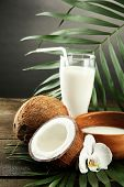Coconut with glass of milk,  on wooden table, on grey background