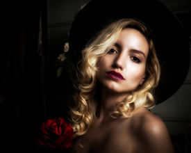 picture of senorita  - A very attractive and glamorous young blond woman holds roses and stares lovingly into the camera.