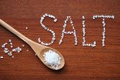 stock photo of sea salt  - Sea salt in wooden spoon and letters from salt crystals - JPG