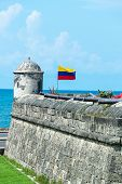 stock photo of fortified wall  - Defensive wall of Cartagena with a Colombian flag waving and several cannons visible in the old town of Cartagena Colombia - JPG
