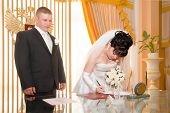 Pretty pair signing document of marriage