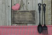 Blank wood sign with red gingham tablecloth, heart and cast iron spoon and fork