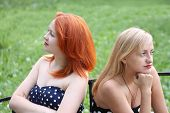 Two Beautiful Girls Sit On Bench And Take Offense At Each Other In Park At Summer Day