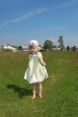 Little Barefoot Girl Plays Shows Blade Of Grass At Green Meadow Near Village At Summer Sunny Day