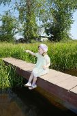 Pretty Little Girl Sits, Shows Thumb And Wonders On Small Bridge In Village At Summer Sunny Day