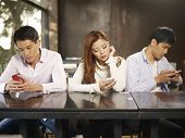 foto of inappropriate  - young people playing with smartphones and ignoring each other.