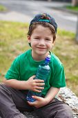 Little Boy Sitting With Bottle Of Water