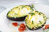 stock photo of avocado  - Eggs with cheddar cheese baked in fresh avocados and garnished with chives - JPG