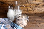 Homemade granola in glass jar, jugs with milk and fresh apple, on color wooden background