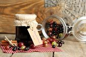 Ripe blackcurrants and gooseberries in glass jar with tasty jam, on wooden background.