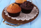 Tasty muffins on tray, on color wooden background