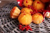 Tasty muffins with red currant on wicker mat background