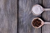 Salt and pepper in spoon on wooden table close-up