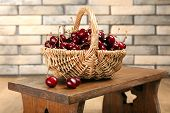 Fresh cherries in basket on wall background