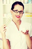 Beautiful woman druggist is holding some tablets.Healthcare concept.