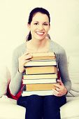 Smiling woman is holding many books. Indoor.