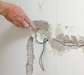 Male Hand Repairs Wall With Spackling Paste.