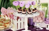 stock photo of buffet  - Delicious sweet buffet with cupcakes glasses and other desserts - JPG