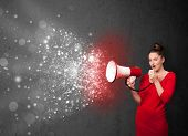 Woman shouting into megaphone and glowing energy particles explode concept