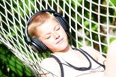 Boy Lying In A Hammock And Listen To Music On Headphones. Summer Vacation Concept.