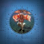 Beautiful woman dancing underwater. Submarine window with view to sea.